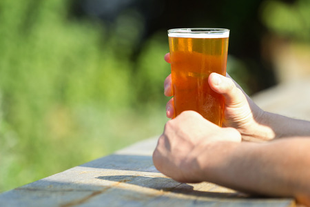 Glass of craft beer in hands on wooden table against isolated green forest in the background Stock Photo