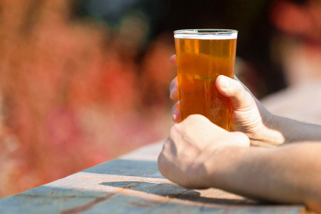 Glass of craft beer in hands on wooden table against isolated autumn forest in the background