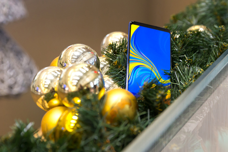Mobile smartphone displayed as a gift in Christmas decoration. Digital gadget with colorful screen for internet and telecommunication.