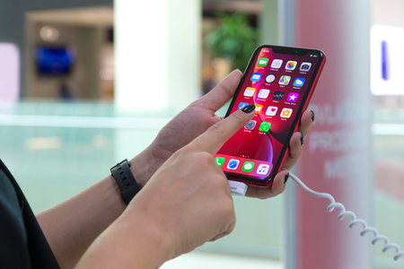 Belgrade, Serbia - October 26, 2018: New Apple iPhone XR is displayed with home screen in hands. Testing apps on mobile smartphone, with a finger in electronic store Editorial