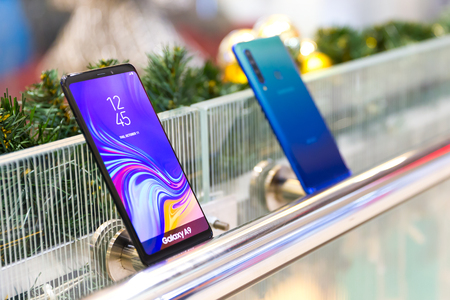 Belgrade, Serbia - November 30, 2018: Newly launched Samsung Galaxy A9 mobile smartphones are displayed in electronic store. Gadgets showing front and rear side against isolated christmas decoration in the background.