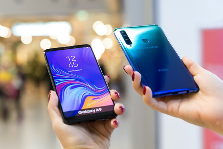 Belgrade, Serbia - November 30, 2018: Newly launched Samsung Galaxy A9 mobile smartphone is displayed from both sides in hands isolated on blurry background. Editorial
