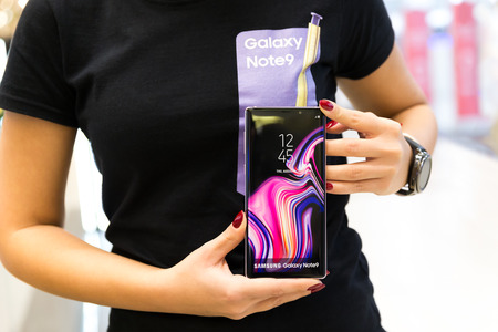 Belgrade, Serbia - November 30, 2018: New Samsung Galaxy Note 9 mobile smartphone promoting by promo team. Girl hand holding Flagship gadget in electronic store.