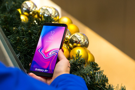 Belgrade, Serbia - December 14, 2018: New Samsung Galaxy J6+ mobile smartphone is displayed in hand. Christmas decoration in the background.