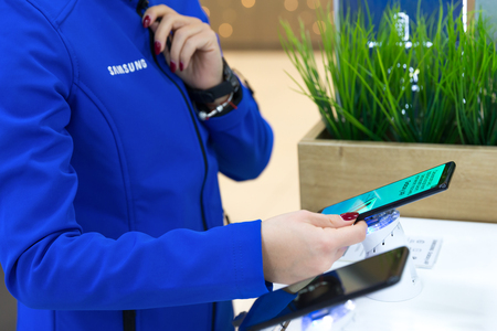 Belgrade, Serbia - December 14, 2018: New Samsung Galaxy A9 mobile smartphone promoting by promo team. Girl wears blue jacket with brand logo and testing digital gadget in electronic store.