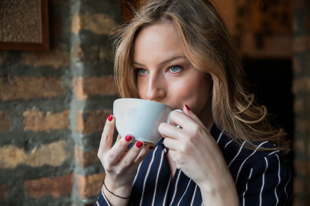 Portrait of beautiful young woman drinking coffee in cafe. Attractive girl holding white cup in hands. Stock Photo