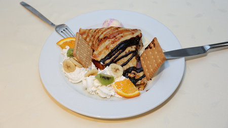 Close up of pancake served on plate with fork and knife on the kitchen table. Dessert arranged with fresh fruits, biscuits and chocolate topping. Stock Photo