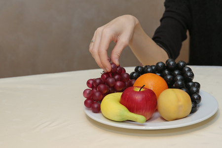 Woman picking grapes from plate with her hand. Close up detail of fresh fruit on the table. Healthy meal. Stock Photo