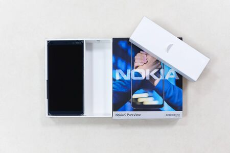 Belgrade, Serbia - May 08, 2019: New Nokia 9 Pure View mobile smartphone is displayed with original cardboard box on isolated white background. Editorial