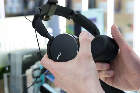 Belgrade, Serbia - Jun 06, 2019: New black AKG headphones are shown in hands in electronic store.