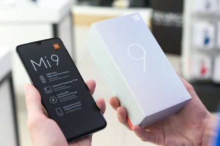 Belgrade, Serbia - Jun 06, 2019: New Xiaomi Mi 9 mobile smartphone is displayed with original cardboard box in hands.