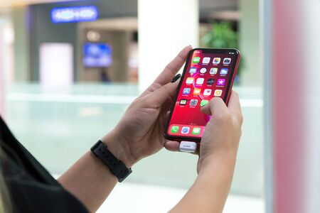 Belgrade, Serbia - October 26, 2018: New Apple iPhone XR mobile smartphone is displayed with apps on the screen in hand. Finger typing on digital gadget in electronic store.