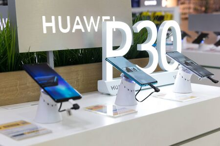 Belgrade, Serbia - April 05, 2019: New Huawei P30 mobile smartphones are shown on retail display in electronic store. Huawei and P30 logo in the background. Editorial