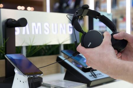 Belgrade, Serbia - Jun 06, 2019: New black AKG headphones are shown in hands on retail display in electronic store. S10 mobile smartphones and Samsung brand logo in the background.