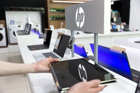 Belgrade, Serbia - Jun 06, 2019: HP laptop computer is shown in hands on retail display. Testing of new notebook gadget in electronic store. Brand logo in the background.