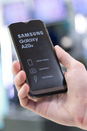 Belgrade, Serbia - Jun 06, 2019: New Samsung Galaxy A20e mobile smartphone is shown in hand on isolated background.