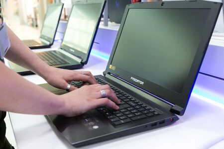 Belgrade, Serbia - May 08, 2019: New Acer Predator laptop is shown on retail display. Girl testing digital gadget in electronic store. Hands on keyboard.