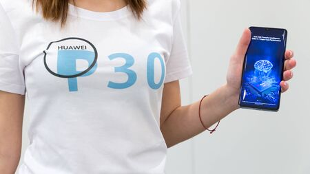 Belgrade, Serbia - March 27, 2019: Promo team girl presenting Huawei P30 Pro mobile smartphone. New gadget shows Kirin 980 performances on the screen. Brand logo on promo T-shirt.