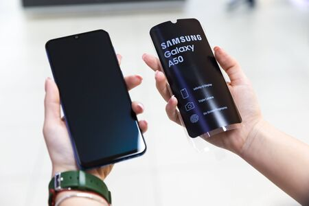 Belgrade, Serbia - April 05, 2019: New Samsung Galaxy A50 mobile smartphone is displayed in hands on isolated background.