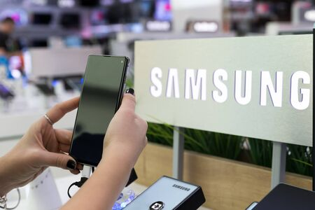 Belgrade, Serbia - February 21, 2019: New Samsung Galaxy S10 smartphone is shown in hand on retail display. Brand logo in the background.