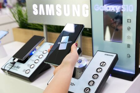 Belgrade, Serbia - February 21, 2019: New Samsung Galaxy S10+ smartphone is shown in hand on retail display. Girl holds mobile gadget in electronic store.