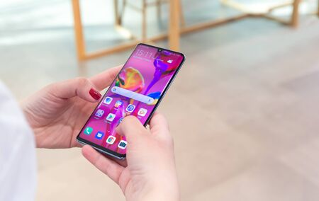 Belgrade, Serbia - March 27, 2019: New Huawei P30 Pro Smartphone is displayed with home screen in electronic store. Girl testing new gadget in hands. Editorial