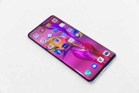 Belgrade, Serbia - March 27, 2019: Newly launched Huawei P30 Pro mobile smartphone is displayed from above on isolated white background. Flagship gadget with apps on the screen.