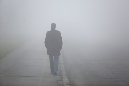 Alone Man from back walking through the fog on street 스톡 콘텐츠