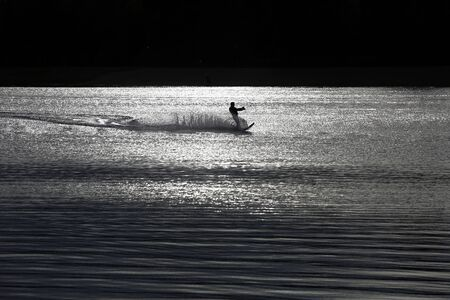 waterskiing: Sunset waterskiing wakeboarder silhouette sprays wate