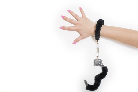 Beautiful female hand locked in the black handcuffs in studio Stock Photo