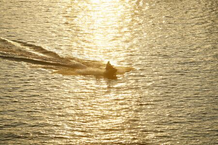 jetski: Silhouette of People on Jet-ski against the Sunset in River