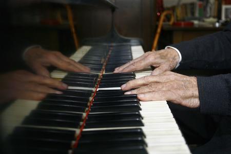 persona mayor: El hombre de edad que juega el piano con sus manos en ruinas
