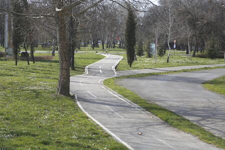 walking paths: Paved walking paths and bicycle trail in nature with green grass Stock Photo