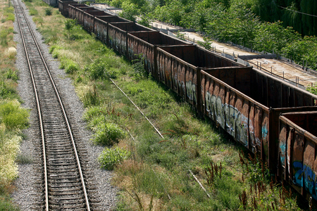 rust covered: Cargo train platform railway tracks in a rural scene, Empty railway containers for transportation covered with a rust