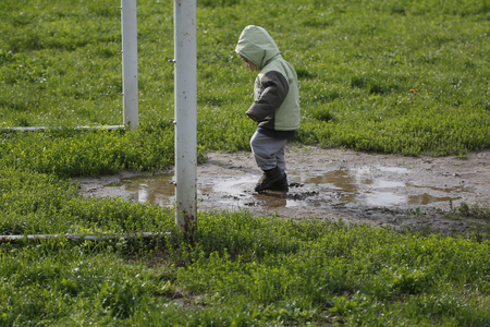 two years: Two years child walk and playing in mud puddle in park