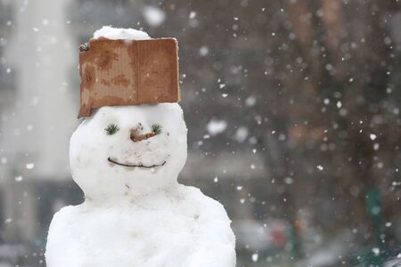 frozen winter: Kid made Funny snowman in the park with cap made of cardboard Stock Photo