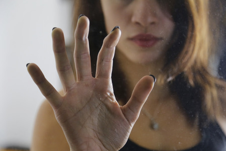 Girl holding hand on door glass showing the fear Stock Photo