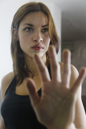 self harm: Girl holding hand on door glass showing the fear Stock Photo