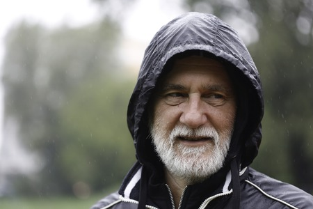 Mature caucasian gray man with beard and mustache in a park standing in the rain wearing hooded black sport jacket looking away from the camera with blurry background Stock Photo