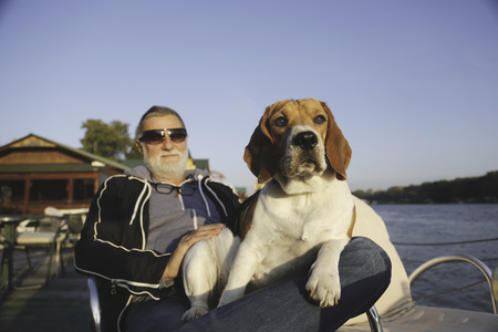 hedonism: Older caucasian man wearing sunglasses and a beard in dark jacket and jeans on a riverbank enjoying a mild spring day under a blue sky with no clouds holding his cute white-brown dog in his lap and a wooden boat house in the background