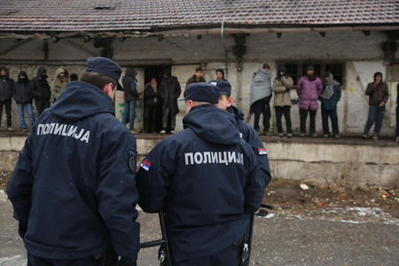 guarded: Belgrade, Serbia - January 17, 2017: Serbian Police guarded migrants. Migrant have occupied an abandoned customs warehouse in Belgrade as they seek ways to move to EU.