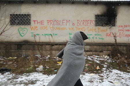Belgrade, Serbia - January 17, 2017: Migrant passes by graffiti. Migrant have occupied an abandoned customs warehouse in Belgrade as they seek ways to move to EU.