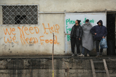 Belgrade, Serbia - January 17, 2017: Migrant next to graffiti for help. Migrant have occupied an abandoned customs warehouse in Belgrade as they seek ways to move to EU.