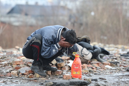 Belgrade, Serbia - January 14, 2017: Refugee washing his face outside on a cold winter day. Migrant have occupied an abandoned customs warehouse in Belgrade in the way to EU.