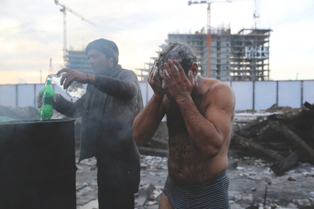 abandoned warehouse: Belgrade, Serbia - January 14, 2017: Refugees washing themselves outside on a cold winter day. Migrant have occupied an abandoned customs warehouse in Belgrade in the way to EU. Editorial