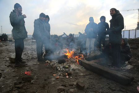 abandoned warehouse: Belgrade, Serbia - January 14, 2017: Refugee heating by the fire outside. Migrant have occupied an abandoned customs warehouse in Belgrade in the way to EU. Editorial