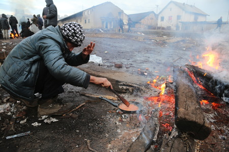 abandoned warehouse: Belgrade, Serbia - January 14, 2017: Refugee cooking lunch by the fire outside. Migrant have occupied an abandoned customs warehouse in Belgrade in the way to EU.
