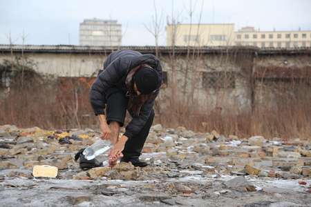 belgrade: Belgrade, Serbia - January 14, 2017: Refugee washing the feet outside on a cold winter day. Migrant have occupied an abandoned customs warehouse in Belgrade in the way to EU. Editorial