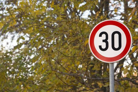 Speed limit thirty sign next to a school park. Trees in the background. Stock Photo