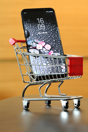 BELGRADE ,SERBIA - JANUARY 08, 2018: Newest Smartphone Samsung Galaxy S8 Plus in small metal shopping cart. Editorial